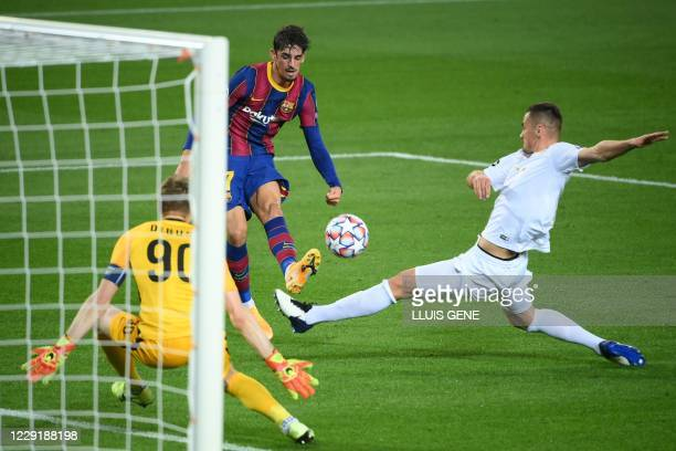 Barcelona's Portuguese forward Francisco Trincao challenges Ferencvaros' Bosnian defender Adnan Kovacevic and Ferencvaros' Hungarian goalkeeper Denes...
