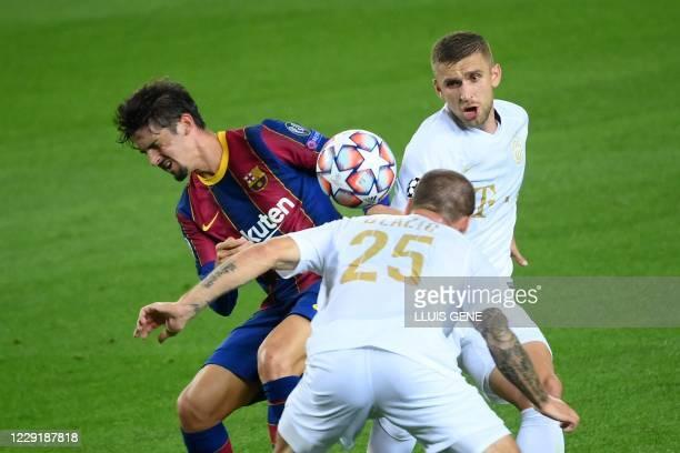Barcelona's Portuguese forward Francisco Trincao challenges Ferencvaros' Slovenian defender Miha Blazic and Ferencvaros' Bosnian midfielder Eldar...