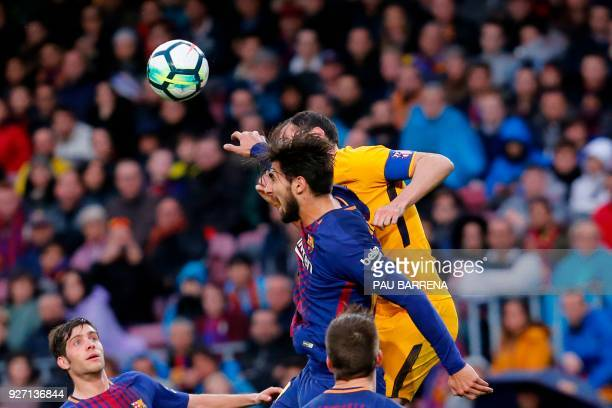 Barcelona's Portuguese midfielder Andre Gomes and Atletico Madrid's Uruguayan defender Diego Godin jump for the ball during the Spanish league...