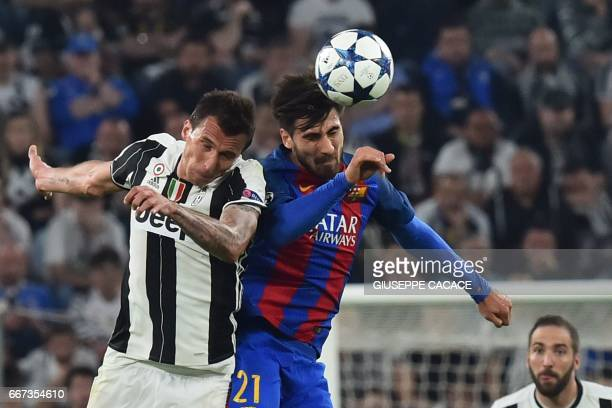 Barcelona's Portuguese midfielder Andre Gomes and Juventus' forward from Croatia Mario Mandzukic jump for the ball during the UEFA Champions League...