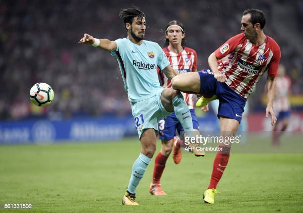 Barcelona's Portuguese midfielder Andre Gomes vies with Atletico Madrid's Uruguayan defender Diego Godin during the Spanish league football match...