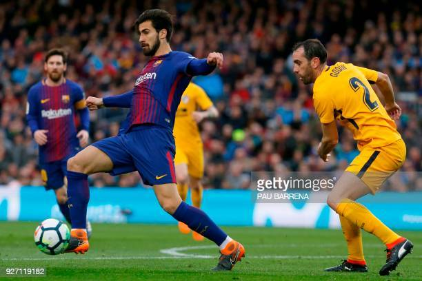 Barcelona's Portuguese midfielder Andre Gomes vies with Atletico Madrid's Uruguayan defender Diego Godin during the Spanish league football match FC...