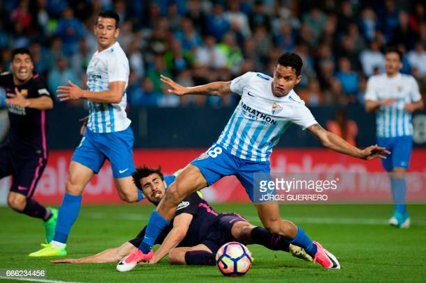 Barcelona's Portuguese midfielder Andre Gomes vies with Malaga's Venezuelan defender Roberto Jose Rosales during the Spanish league football match...