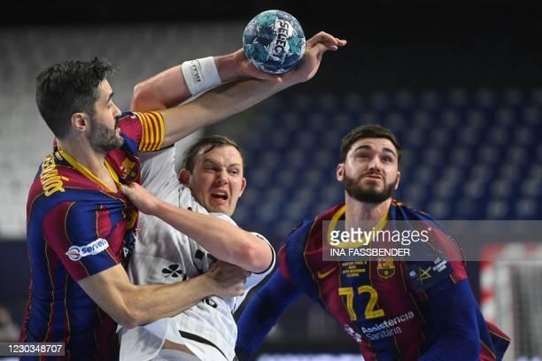 Barcelona's Raul Entrerrios and Kiel's Sander Sagosen vie for the ball during the handball final match Barca v THW Kiel at the EHF Pokal men's...