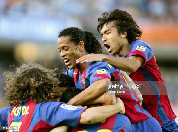 Barcelona`s Ronaldihno Giovanni Van Bronckhorst and Carles Puyol celebrate with Ludovic Giuly after he scored a goal during a La Liga soccer match...