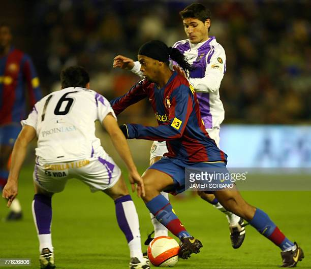 Barcelona's Ronaldinho fights for the ball with Valladolid Pedro Lpez and Vivar Dorado during a Spanish league football match at Zorrila stadium in...