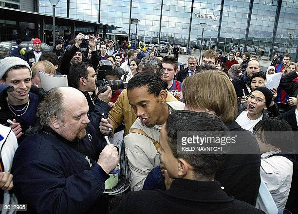 Barcelona's Ronaldinho is welcomed by fans as his team arrives at Copenhagen airport 25 February 2004 on the eve of his team's UEFA match against the...