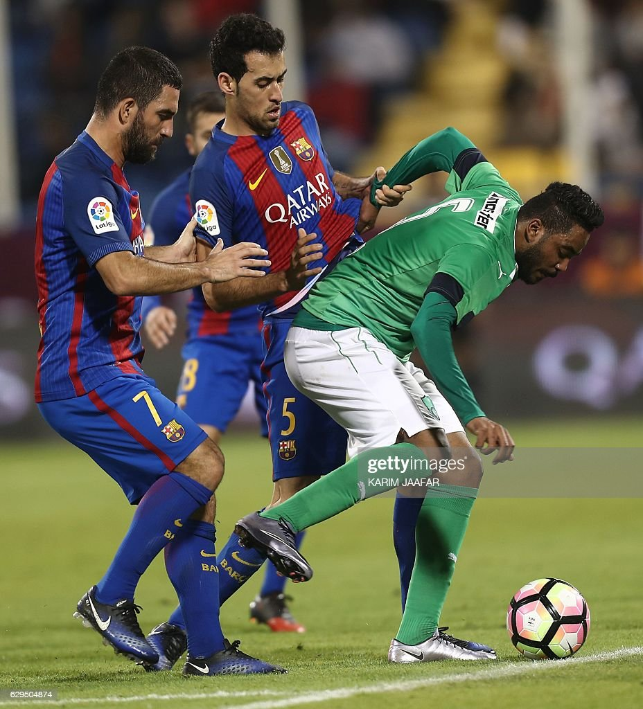 FC Barcelona's Sergio Busquets and Arda Turan (L) vie for the ball with Al-Ahly's Ali al-Zubaidi during a friendly football match between FC Barcelona and Saudi Arabia's Al-Ahli FC on December 13, 2016 in the Qatari capital Doha. Goals from Luiz Suarez, Lionel Messi and Neymar helped Barcelona beat Saudi champions Al-Ahli 5-3 in a thrilling friendly in Doha. The superstar trio all scored by the 17th minute, helping the Spanish giants to stroll into an early three-goal lead. JAAFAR