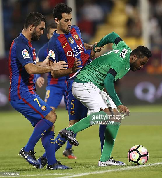 FC Barcelona's Sergio Busquets and Arda Turan vie for the ball with AlAhly's Ali alZubaidi during a friendly football match between FC Barcelona and...
