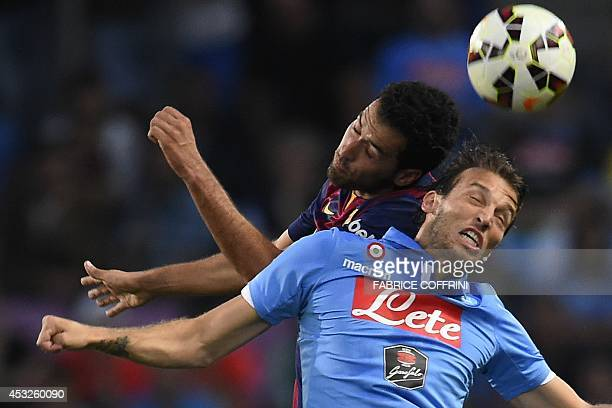 Barcelona's Sergio Busquets heads the ball with Napoli's Spanish forward Michu during a friendly football match between Barcelona and Napoli in...