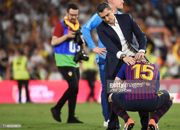 Barcelona's Spanish coach Ernesto Valverde conforts Barcelona's French defender Clement Lenglet at the end of the 2019 Spanish Copa del Rey final...