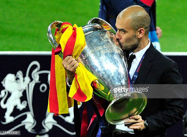 Barcelona's Spanish coach Josep Guardiola kisses the trophy at the end of the UEFA Champions League final football match FC Barcelona vs Manchester...