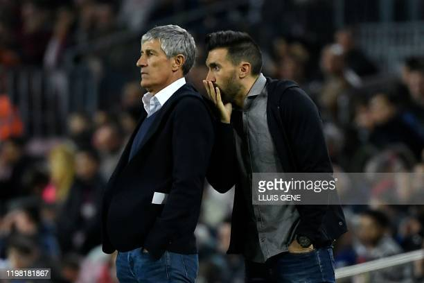 Barcelona's Spanish coach Quique Setien listens to his assistant coach Eder Sarabia during the Spanish league football match between FC Barcelona and...