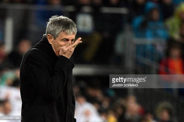Barcelona's Spanish coach Quique Setien rubs his face during the Spanish League football match between Real Madrid and Barcelona at the Santiago...