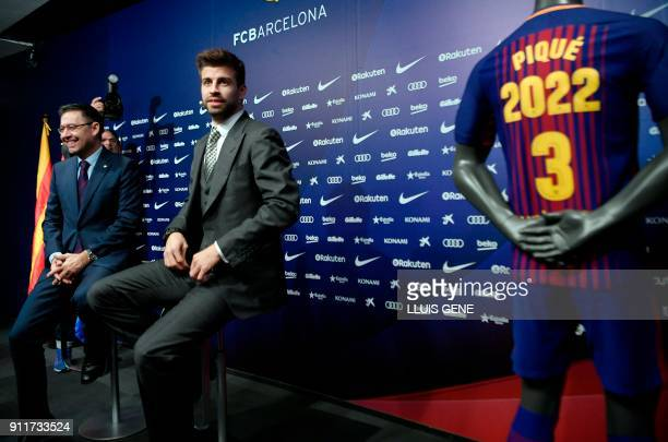 Barcelona's Spanish defender Gerard Pique and Barcelona FC president Josep Maria Bartomeu give a press conference to officially announce his contract...