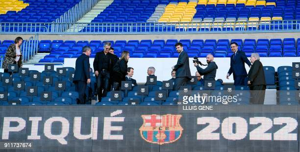 Barcelona's Spanish defender Gerard Pique and Barcelona FC president Josep Maria Bartomeu walk on stands before giving a press conference to...