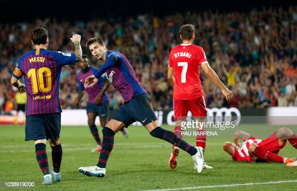 Barcelona's Spanish defender Gerard Pique celebrates a goal with Barcelona's Argentinian forward Lionel Messi during the Spanish league football...