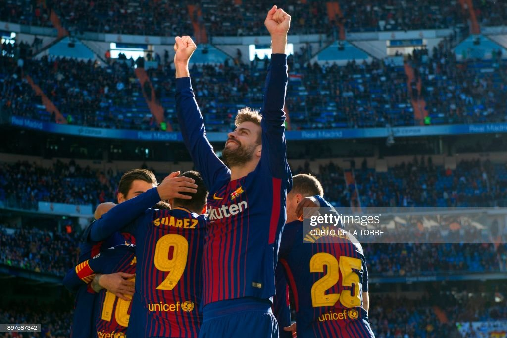 TOPSHOT - Barcelona's Spanish defender Gerard Pique celebrates after Barcelona's Spanish midfielder Aleix Vidal scored during the Spanish League 'Clasico' football match Real Madrid CF vs FC Barcelona at the Santiago Bernabeu stadium in Madrid on December 23, 2017. /