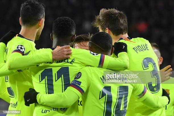 Barcelona's Spanish defender Gerard Pique celebrates with his teammates after scoring during the UEFA Champions League football match between PSV...