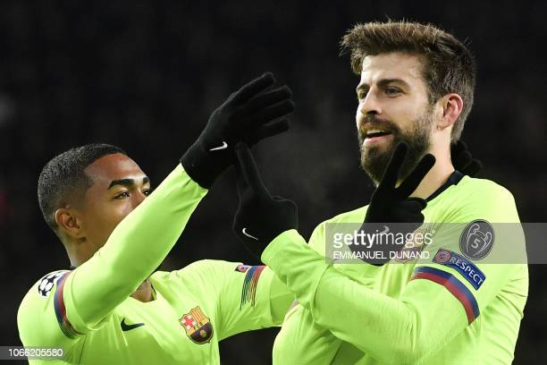 Barcelona's Spanish defender Gerard Pique celebrates with his teammate Barcelona's Brazilian forward Malcom after scoring during the UEFA Champions...