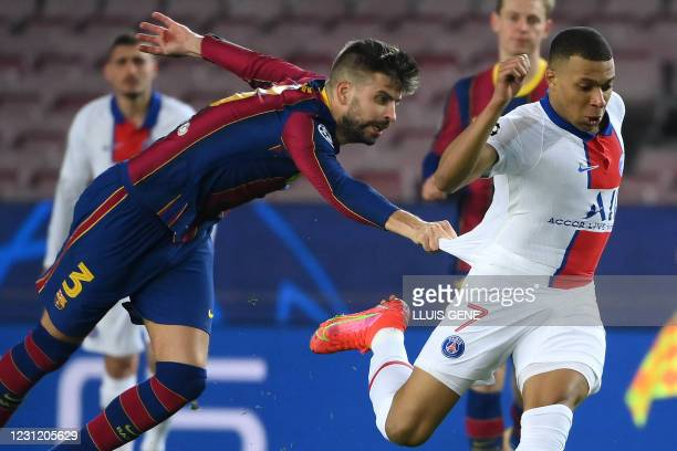 Barcelona's Spanish defender Gerard Pique challenges Paris Saint-Germain's French forward Kylian Mbappe during the UEFA Champions League round of 16...