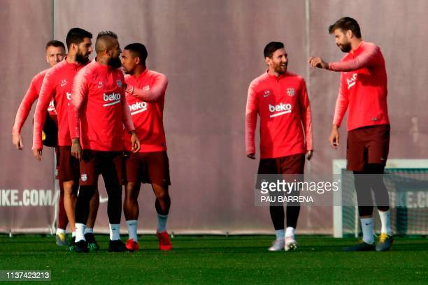 Barcelona's Spanish defender Gerard Pique chats with Barcelona's Argentinian forward Lionel Messi during a training session at the Joan Gamper Sports...