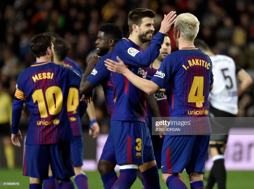 Barcelona's Spanish defender Gerard Pique (2R) congratulates Barcelona's Croatian midfielder Ivan Rakitic after scoring their team's second goal during the Spanish 'Copa del Rey' (King's cup) second leg semi-final football match between Valencia CF and FC Barcelona at the Mestalla stadium in Valencia on February 8, 2018. /