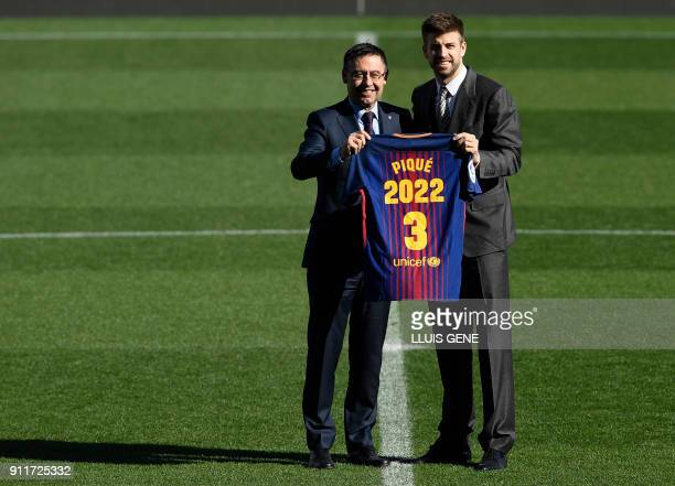 Barcelona's Spanish defender Gerard Pique holds his jersey with Barcelona FC president Josep Maria Bartomeu as they pose during the official...