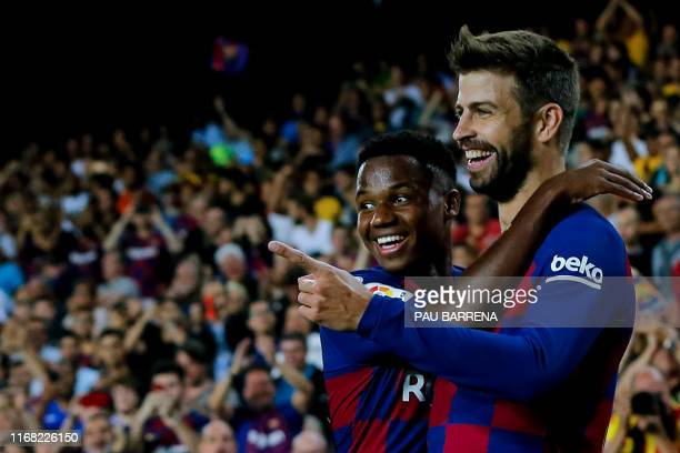 Barcelona's Spanish defender Gerard Pique is congratulated by teammate Barcelona´s Guinea-Bissau forward Ansu Fati after scoring a goal during the...