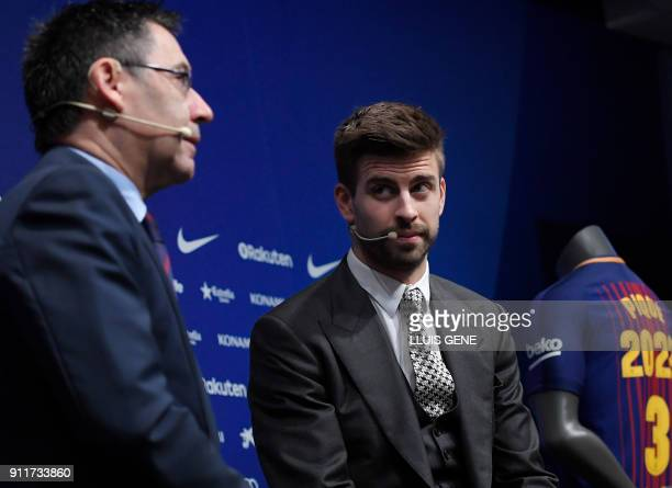 Barcelona's Spanish defender Gerard Pique listens to Barcelona FC president Josep Maria Bartomeu during a press conference to officially announce his...