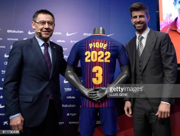 Barcelona's Spanish defender Gerard Pique poses beside his jersey and Barcelona FC president Josep Maria Bartomeu during the official announcement of...