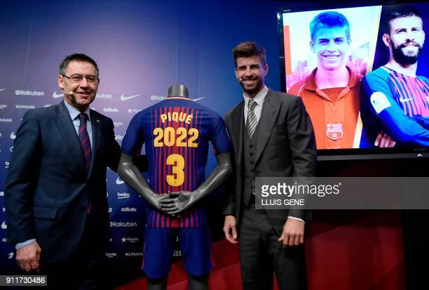 TOPSHOT Barcelona's Spanish defender Gerard Pique poses beside his jersey and Barcelona FC president Josep Maria Bartomeu during the official...