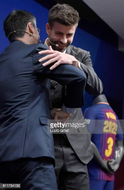 Barcelona's Spanish defender Gerard Pique shakes hands with Barcelona FC president Josep Maria Bartomeu during a press conference to officially...