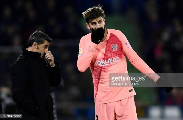 Barcelona's Spanish defender Gerard Pique speaks with Barcelona's Spanish coach Ernesto Valverde during the Spanish League football match between...