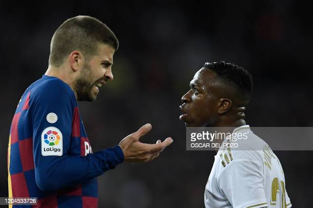Barcelona's Spanish defender Gerard Pique talks with Real Madrid's Brazilian forward Vinicius Junior during the Spanish League football match between...