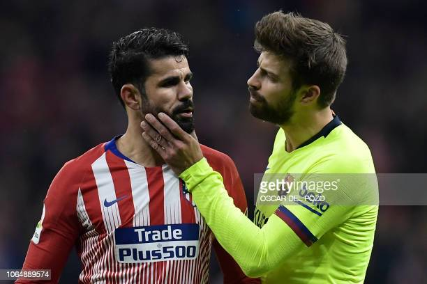 Barcelona's Spanish defender Gerard Pique tries to calm down Atletico Madrid's Spanish forward Diego Costa as he argues with Barcelona's players...