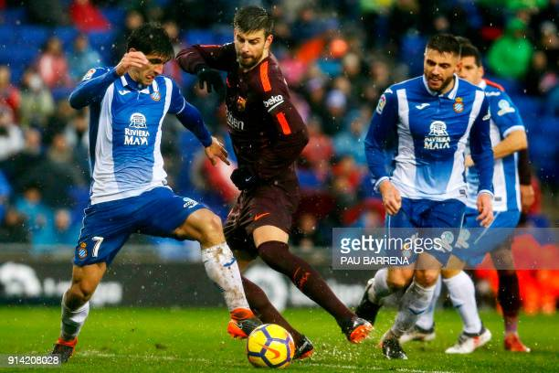 Barcelona's Spanish defender Gerard Pique vies with Espanyol's Spanish forward Gerard Moreno during the Spanish league football match between RCD...