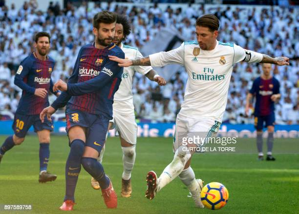 Barcelona's Spanish defender Gerard Pique vies with Real Madrid's Spanish defender Sergio Ramos during the Spanish League 'Clasico' football match...