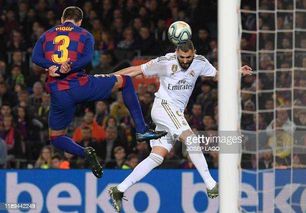 TOPSHOT Barcelona's Spanish defender Gerard Pique vies woith Real Madrid's French forward Karim Benzema during the El Clasico Spanish League football...