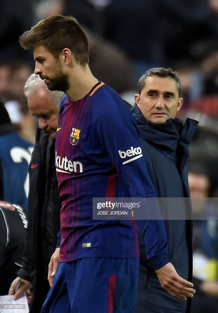 Barcelona's Spanish defender Gerard Pique (L) walks past Barcelona's Spanish coach Ernesto Valverde (R) as he leaves the field during the Spanish 'Copa del Rey' (King's cup) second leg semi-final football match between Valencia CF and FC Barcelona at the Mestalla stadium in Valencia on February 8, 2018. /