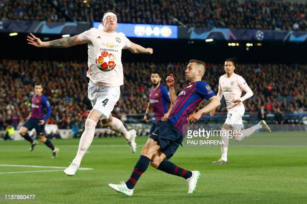 Barcelona's Spanish defender Jordi Alba challenges Manchester United's English defender Phil Jones during the UEFA Champions League quarterfinal...