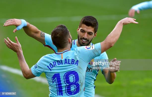 Barcelona's Spanish defender Jordi Alba is congratulated by teammate Uruguayan forward Luis Suarez for scoring the team's second goal during the...