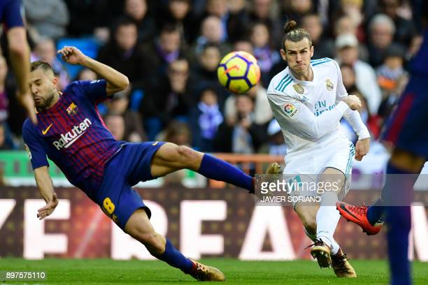 Barcelona's Spanish defender Jordi Alba veis with Real Madrid's Welsh forward Gareth Bale during the Spanish League 'Clasico' football match Real...