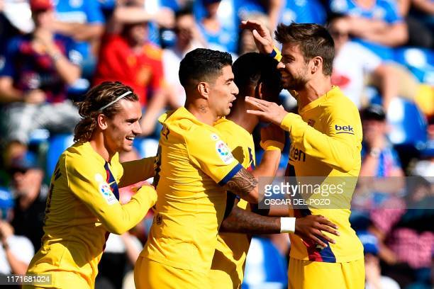 Barcelona's Spanish defender Junior Firpo celebrates with Barcelona's French forward Antoine Griezmann Barcelona's Uruguayan forward Luis Suarez and...