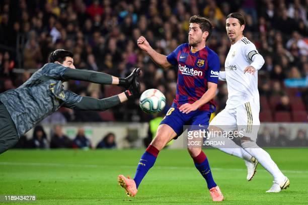 Barcelona's Spanish defender Sergi Roberto challenges Real Madrid's Spanish defender Sergio Ramos and Real Madrid's Belgian goalkeeper Thibaut...