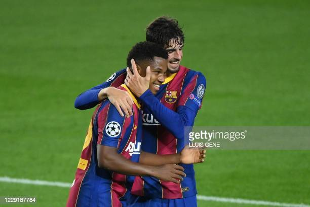 Barcelona's Spanish forward Ansu Fati celebrates with Barcelona's Portuguese forward Francisco Trincao after scoring a goal during the UEFA Champions...