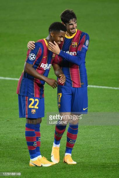 Barcelona's Spanish forward Ansu Fati celebrates with Barcelona's Portuguese forward Francisco Trincao after scoring a goal during the UEFA Champions...
