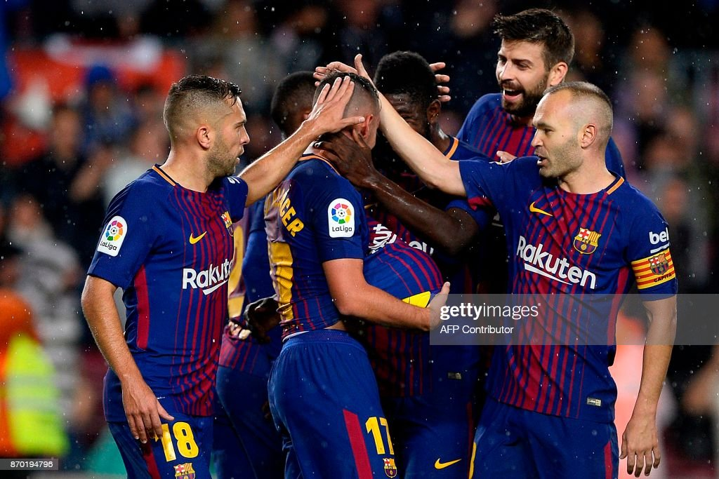 Barcelona's Spanish forward Paco Alcacer (C) celebrates with teammates after scoring a goal during the Spanish league football match FC Barcelona vs Sevilla FC at the Camp Nou stadium in Barcelona on November 4, 2017. / AFP PHOTO / Josep LAGO