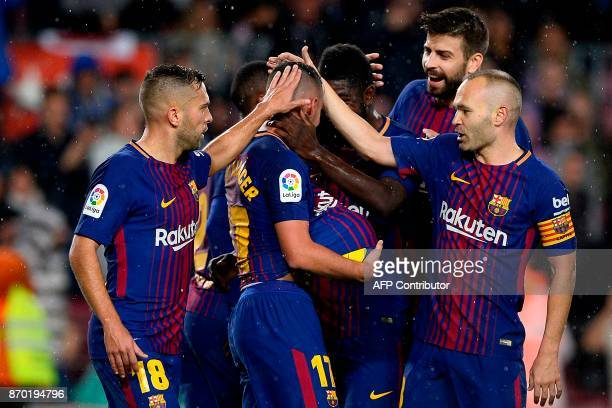 Barcelona's Spanish forward Paco Alcacer celebrates with teammates after scoring a goal during the Spanish league football match FC Barcelona vs...