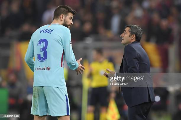 FC Barcelona's Spanish head coach Ernesto Valverde speaks with FC Barcelona's Spanish defender Gerard Pique during the UEFA Champions League...